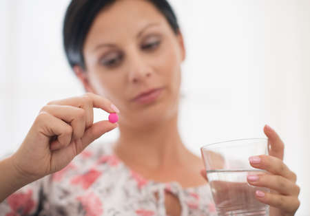 Closeup on pill and glass of water in hand of concerned young woman Stock Photo - 18493197