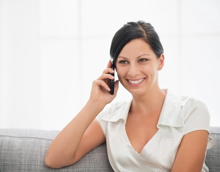 Smiling young woman sitting on couch and talking cell phone Stock Photo - 18493214