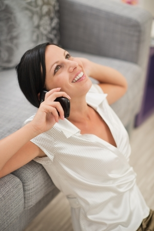 Happy young woman sitting on floor and talking mobile phone photo