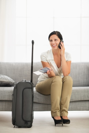 Happy young woman in living room with travel bag talking mobile phone photo