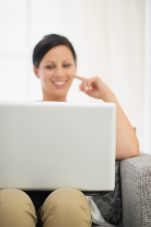 topicality: Closeup on laptop and happy young woman in background Stock Photo