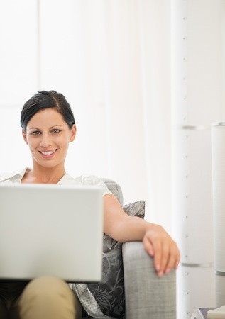 Smiling young woman using laptop photo
