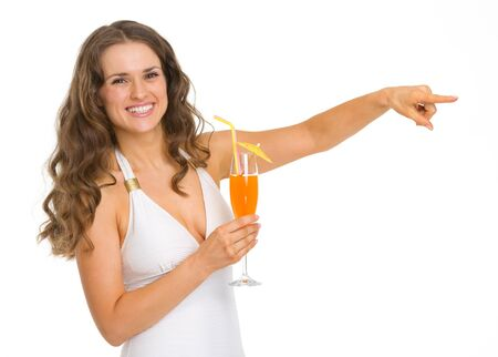 Smiling young woman in swimsuit with cocktail pointing on copy space Stock Photo - 18625023