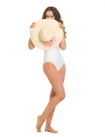 Full length portrait of young woman in swimsuit hiding behind hat Stock Photo - 18625129