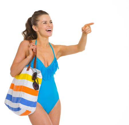 Happy young woman in swimsuit pointing on copy space Stock Photo - 18625081