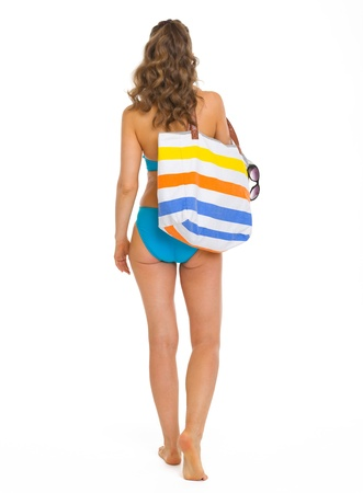 Young woman in swimsuit with beach bag going straight   rear view Stock Photo - 18625080