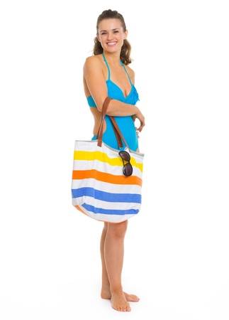Full length portrait of smiling young woman in swimsuit with beach bag Stock Photo - 18625140