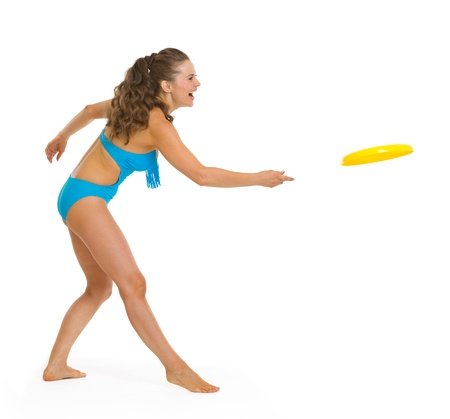 Happy young woman in swimsuit playing with frisbee Stock Photo - 18625142