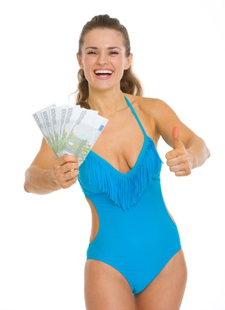 Smiling young woman in swimsuit showing fan of euros Stock Photo - 18625017