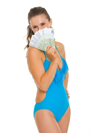 Smiling young woman in swimsuit hiding behind fan of euros Stock Photo - 18625022