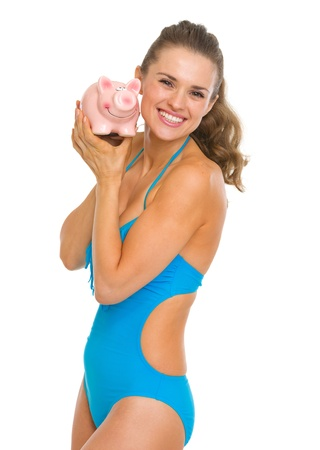 Happy young woman in swimsuit showing piggy bank Stock Photo - 18624983