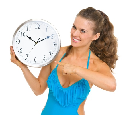 Smiling young woman in swimsuit pointing on clock Stock Photo - 18625010