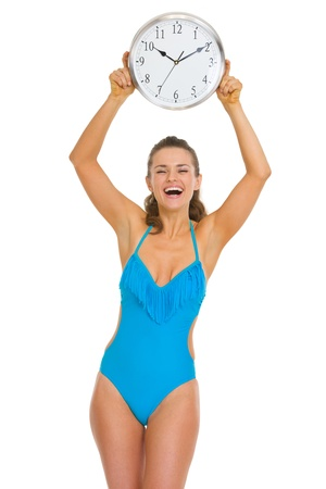 Smiling young woman in swimsuit showing clock Stock Photo - 18625084