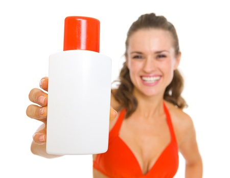 Smiling young woman in swimsuit showing sun block creme Stock Photo - 18625143