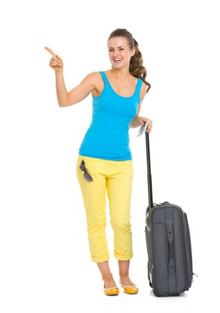 Smiling young tourist woman with wheel bag pointing on copy space Stock Photo - 18660701