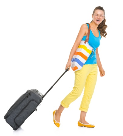 Smiling young tourist woman with wheel bag going sideways photo