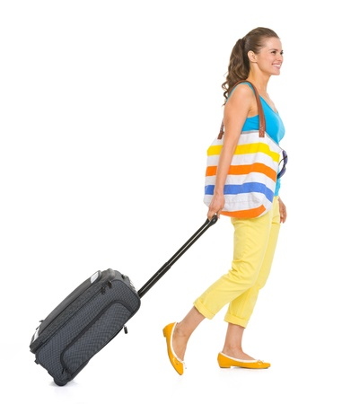 Young tourist woman with wheel bag going sideways photo