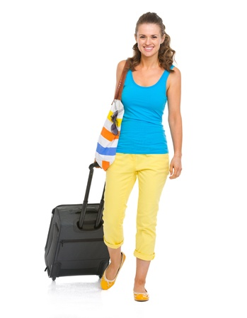 Smiling young tourist woman with wheel bag going straight photo