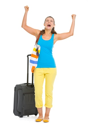 Happy young tourist woman with wheel bag rejoicing photo