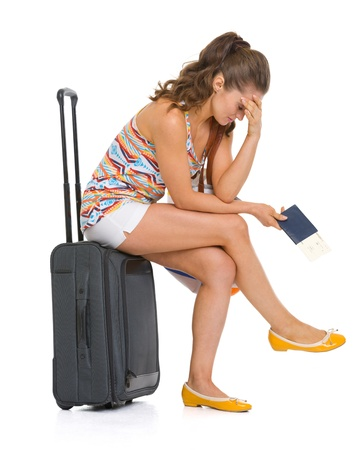Stressed young tourist woman sitting on wheel bag Stock Photo