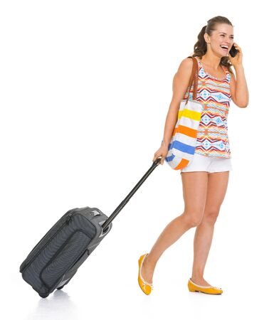 Happy young tourist woman with wheel bag walking and talking mobile phone photo