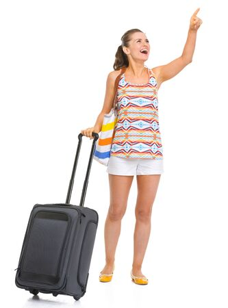 Smiling young tourist woman with wheel bag pointing on copy space Stock Photo - 18660709