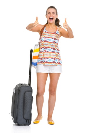 Happy young tourist woman with wheel bag showing thumbs up Stock Photo - 18660625