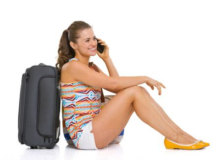 Happy young tourist woman sitting near wheel bag and talking cell phone Stock Photo - 18660616