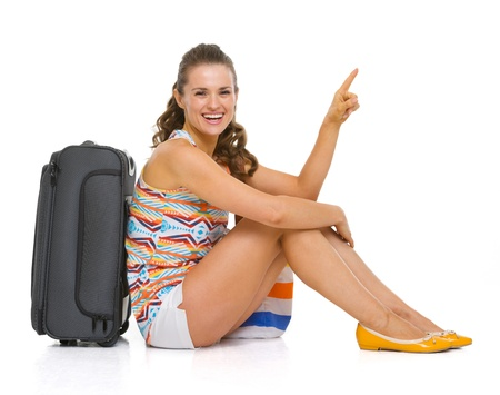 Happy young tourist woman sitting near wheel bag and pointing on copy space Stock Photo - 18660015