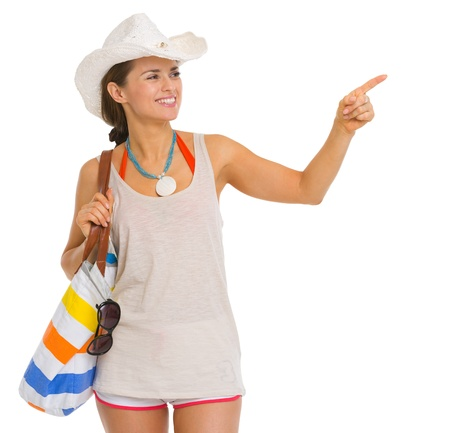 Happy young beach woman in hat pointing on copy space Stock Photo - 18649323