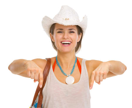 Smiling young beach woman in hat pointing down on copy space Stock Photo - 18660014