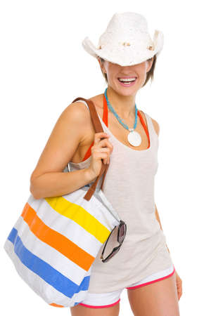 pulled over: Smiling young beach woman with hat pulled over eyes