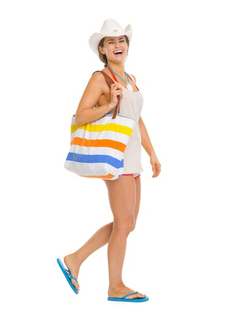 Full length portrait of happy young beach woman in hat going sideways photo