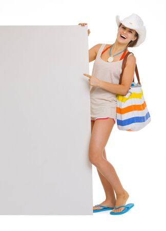 Full length portrait of smiling young beach woman in hat pointing on blank billboard Stock Photo - 18660019