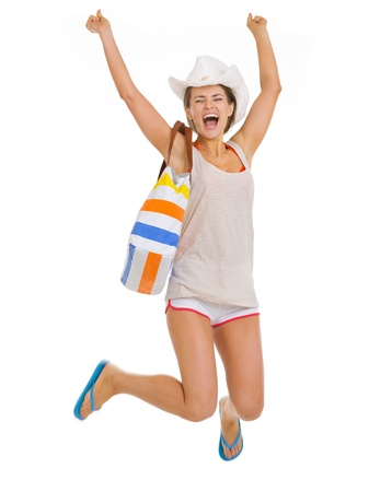 Smiling young beach woman in hat jumping photo
