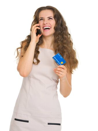 Happy young woman with credit card talking mobile phone Stock Photo - 18788111