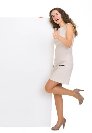 Full length portrait of young woman with blank billboard showing thumbs up Stock Photo - 18788158
