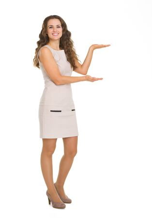 Full length portrait of young woman showing something on empty hands Stock Photo - 18788202