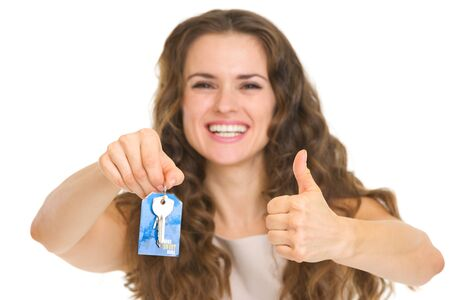 Portrait of happy young woman showing house key and showing thumbs up Stock Photo - 18788160