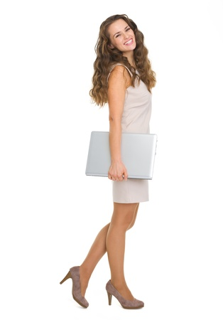 Full length portrait of smiling young woman with laptop Stock Photo - 18788201