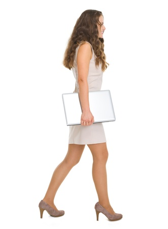 Full length portrait of young woman with laptop going sideways Stock Photo - 18788198