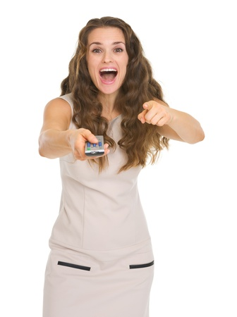 tv remote: Surprised young woman with tv remote control pointing in camera