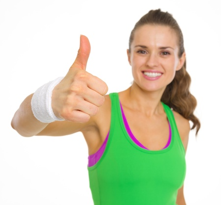 thumbs up woman: Closeup on fitness young woman showing thumbs up Stock Photo