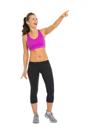 Full length portrait of smiling fitness young woman pointing on copy space Stock Photo - 18911863