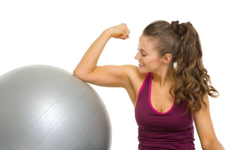 Happy fitness young woman checking biceps photo