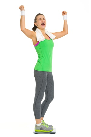 Happy fitness young woman standing on scales and rejoicing success Stock Photo - 18911870