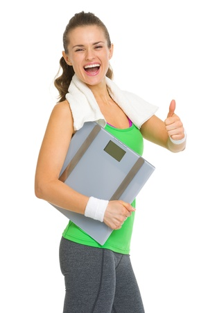 thumbs up woman: Smiling fitness young woman with scales showing thumbs up Stock Photo