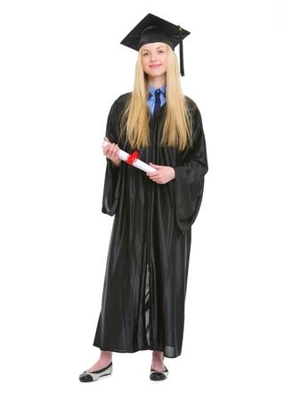 graduacion de universidad: Retrato de cuerpo entero de una mujer joven feliz en el vestido de la graduación con el diploma