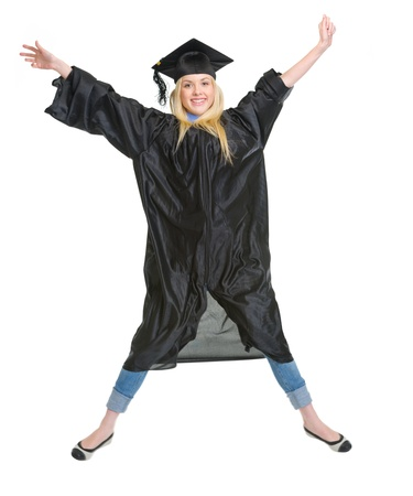 Full length portrait of smiling young woman in graduation gown jumping photo