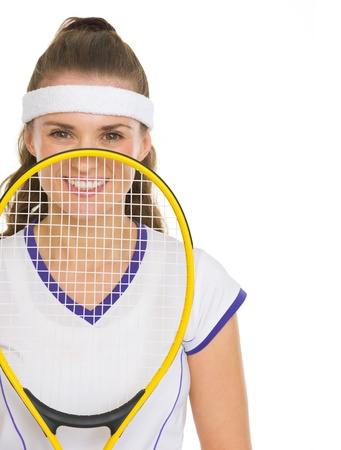 Happy female tennis player holding racket in front of face photo